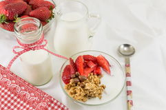 Granola cereals, fresh strawberries and bottle of milk Royalty Free Stock Photo
