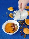Granola con le albicocche e le arance Il latte sta versando nel granola con una brocca di vetro fotografie stock libere da diritti