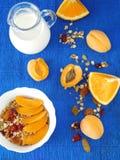 Granola con le bacche secche in una ciotola bianca circondata dalle albicocche, dalle arance e da una brocca di latte Immagini Stock