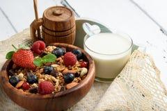 Granola con yogurt naturale, i mirtilli freschi, i dadi ed il miele, fotografie stock