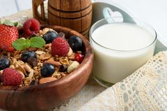 Granola con yogurt naturale, i mirtilli freschi, i dadi ed il miele, fotografia stock