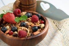 Granola con yogurt naturale, i mirtilli freschi, i dadi ed il miele, immagine stock