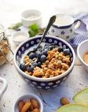 Granola con yogurt naturale, i mirtilli freschi, i dadi ed il miele in una ciotola ceramica su una tavola di legno bianca Prima c immagini stock libere da diritti