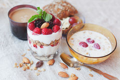 Granola with cream and fresh berries and cup of coffee, typical. Healthy breakfast Royalty Free Stock Photo