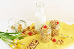 Granola and crunchy with milk. Granola and crispy wholegrain crunchy with dried cherry, fresh milk in the bottle, over yellow linen napkin, wooden background royalty free stock photo