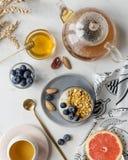 Granola dans le pot avec des myrtilles avec le thé, le miel et le pamplemousse sur le fond de marbre blanc photos libres de droits