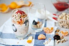 Granola de la avena del yogur con las bayas, el mandarín y las nueces en los tarros de cristal imagen de archivo