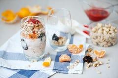 Granola de la avena del yogur con las bayas, el mandarín y las nueces en los tarros de cristal foto de archivo