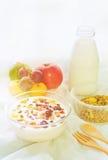 Granola dei grani in una bottiglia per il latte ed in una frutta di vetro su una luce solare bianca del panno di mattina Immagini Stock Libere da Diritti