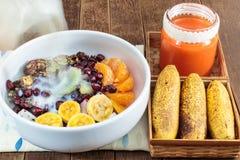 Granola del chocolate con las nueces, las frutas de la mezcla, el jugo de la leche y de zanahoria Imagen de archivo