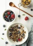 Granola do café da manhã com fundo da madeira da opinião superior dos flocos de milho da framboesa do mirtilo do leite imagens de stock royalty free