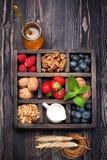 Granola, dokrętki, jagody, miód, mleko w drewnianym pudełku Fotografia Royalty Free