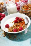 Granola with dried apricot, raspberries and yogurt for breakfast. Granola with dried apricots, raspberries and yogurt for breakfast, vertical top view Stock Photo
