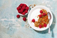 Granola with dried apricot, raspberries and yogurt for breakfast. Granola with dried apricots, raspberries and yogurt for breakfast, top view horizontal Stock Photography
