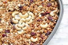 Granola in einer Backform, Acajoubaum in Form des Herzens Chef gießt Olivenöl über frischem Salat in der Gaststätteküche Nahaufna Stockfotografie