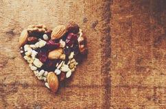 Granola en forme de coeur avec des céréales, les écrous et le raisin sec entiers photographie stock libre de droits
