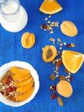 Granola en un cuenco blanco rodeado por los albaricoques y las naranjas Imagen de archivo libre de regalías