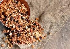 Granola faite maison débordant la cuvette sur la table en bois photographie stock