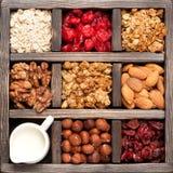 Granola, farina d'avena, dadi, bacche in una scatola di legno Vista superiore Priorità bassa dell'alimento Immagine Stock