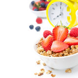 Granola with fresh berries for breakfast and yellow alarm clock Royalty Free Stock Photography