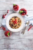Granola and fresh berries. Healthy breakfast with yogurt, homemade granola and fresh berries, top view. White wooden background Royalty Free Stock Image