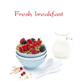 Granola with fresh berries and jug of milk, isolated. On white Royalty Free Stock Image