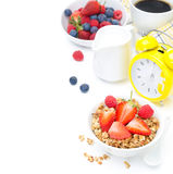 Granola with fresh berries, milk, coffee and yellow alarm clock Royalty Free Stock Images