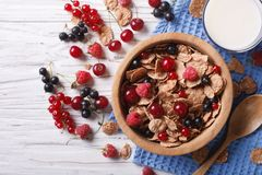 Granola with fresh berries and milk on the table. horizontal top. Granola with fresh berries in a wooden bowl and milk on the table. Horizontal top view Stock Photography