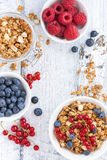 Granola and fresh berries on white wooden background, top view Royalty Free Stock Image