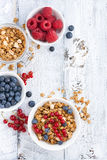 granola and fresh berries on white wooden background, vertical Royalty Free Stock Photography