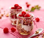 Granola with fresh raspberries and natural yogurt in a glass jar on a wooden pink table. Delicious breakfast or dessert. Healthy eating concept Stock Photography