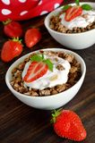 Granola. With fresh strawberry in a white bowl on a dark rustic desk Royalty Free Stock Image