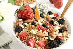 Granola & fruits. Granola bowl: oats, rice, honey, peanuts, almonds, wax berry, white and red raisins, strawberries, glazed orange peel and fig  . Focus on Stock Image