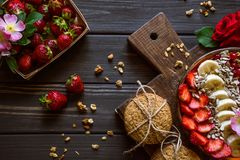 Granola with fruits and berries on a brown board royalty free stock photography