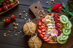 Granola with fruits and berries on a brown board royalty free stock photo