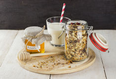 Granola in glass jar, glass of milk and jar of honey on white wo. Oden table Royalty Free Stock Photography