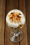 Granola in glass with yogurt on wooden background Royalty Free Stock Images