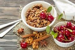 Granola hecho en casa con las cerezas poner crema y rojas para el desayuno Foto de archivo