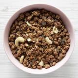 Granola hecho en casa del chocolate con las nueces en un cuenco rosado sobre la superficie de madera blanca, visi?n superior Desd fotos de archivo