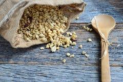 Granola im Leinwand-Sack, der auf hölzernen Hintergrund verschüttet wird Stockfoto