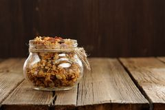 Granola in jar with packing-twine on wooden background with spac Stock Images
