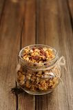 Granola in jar with packing-twine on wooden background with spac Stock Image