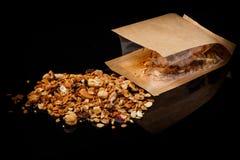 Granola med blandade muttrar och torkad kakao spridda från den kraft påsen royaltyfri fotografi