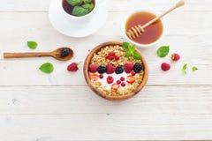 Granola met bessen op witte houten achtergrond stock fotografie