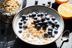 Granola with milk and blueberries in bowl, healthy food royalty free stock images