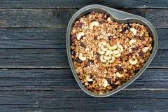 Granola mit Acajoubaum in einer Herz-förmigen Backform Schwarzer Holztisch Stockfotos
