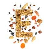 Granola muesli, cereal bar in form of letter E and its ingredi. Ents. Concept of energy reach healthy food, flat lay Royalty Free Stock Images