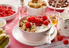 Granola with natural yogurt, fresh raspberries, honey, almond flakes, and poppy seeds in a ceramic bowl on a pink wooden table, to. Granola with natural yogurt Stock Images