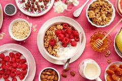 Granola with natural yogurt, fresh raspberries, honey, almond flakes, and poppy seeds in a ceramic bowl on a pink wooden table, to. P view. A delicious and Stock Image