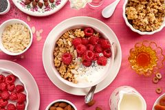Granola with natural yogurt, fresh raspberries, honey, almond flakes, and poppy seeds in a ceramic bowl on a pink wooden table, to. P view. A delicious and Royalty Free Stock Photos